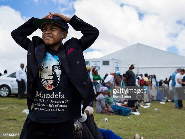 A young boy in a Nelson Mandela T Shirt watches Mandela's funeral on a jumbo television broadcasting the service taking place in the valley below...