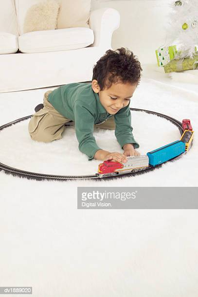 Young Boy in a White Living Room Playing with a Toy Train Set at Christmas
