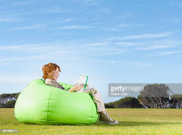Young boy in bean bag reading outdoors