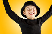 closeup of young boy in black shirt and black hat with victory, winner, yes or done it expression of his face and body gesture with free copy space for the text