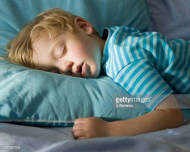 Young boy in blue, peacefully sleeping on a blue pillow