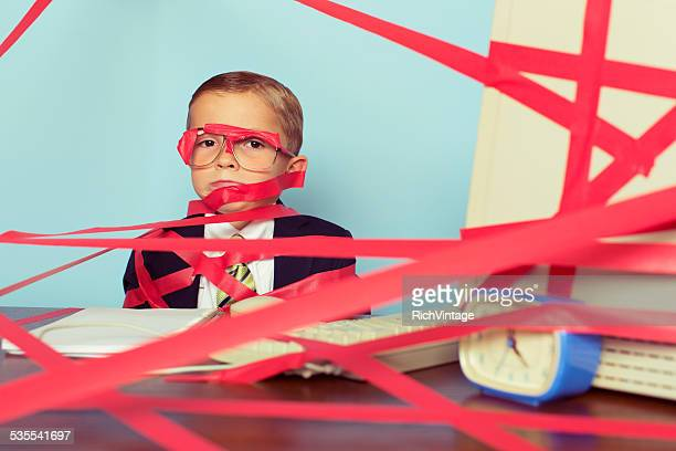 Young Boy in Business Suit Covered in Red Tape