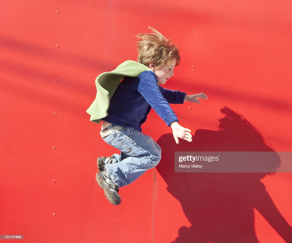 Young boy in cape jumping in mid air. : Stock Photo