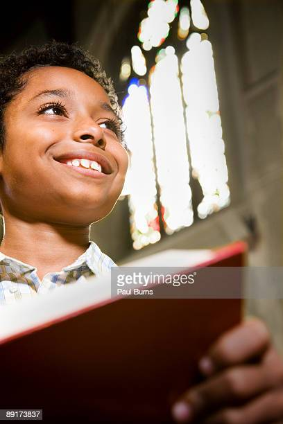 Young Boy in Church Holding Prayer Book