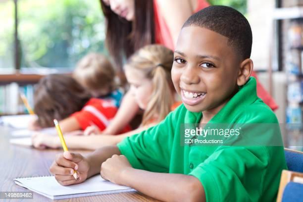 Jeune garçon en classe avec d'autres étudiants et professeurs