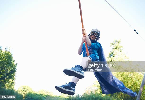 Young boy in fancy dress, on zip wire