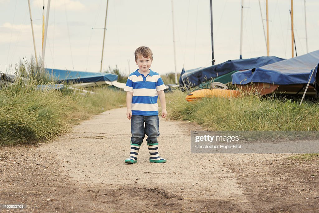 Young boy in front of parked dinghies : Stock Photo