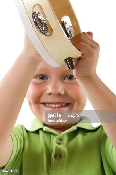 Young boy in green shirt playing a tamborine