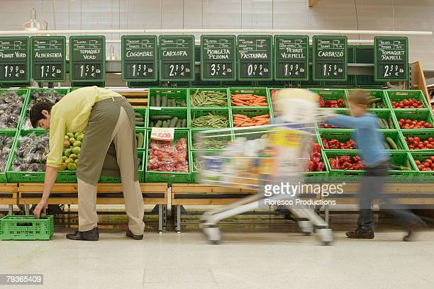 Young boy in grocery store pushing shopping cart by stock boy