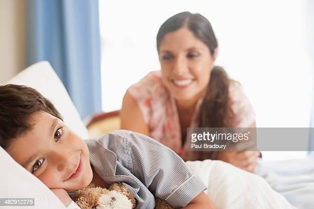 Junge im Krankenhaus Bett lächelnd mit Frau schaut