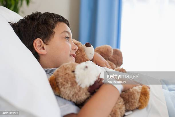 Young boy in hospital bed with teddy bears