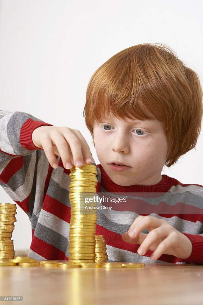 Young boy in kitchen piling up chocolate gold coins : Stock Photo