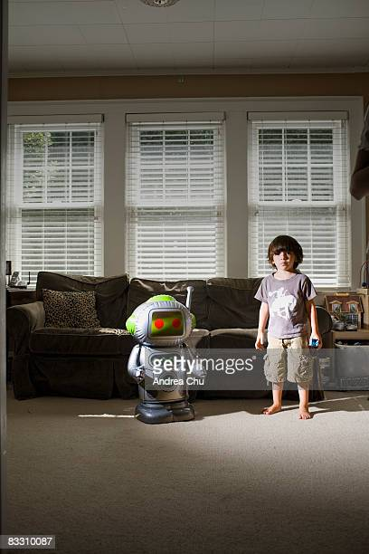 Young boy in living room with toy robot.