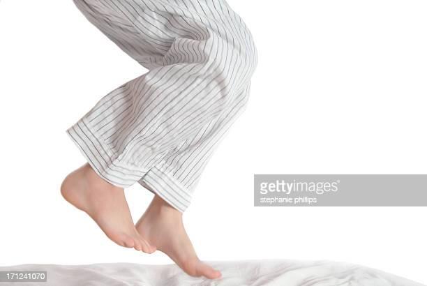 Young Boy en pijama salto en la cama