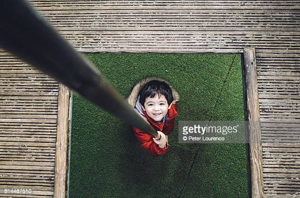 Young boy in playground, holding a sliding pole.