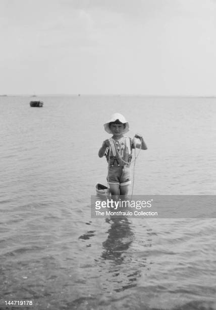 Young boy in shorts and floppy sun hat paddling in the sea and pulling along a small toy boat England circa 1924