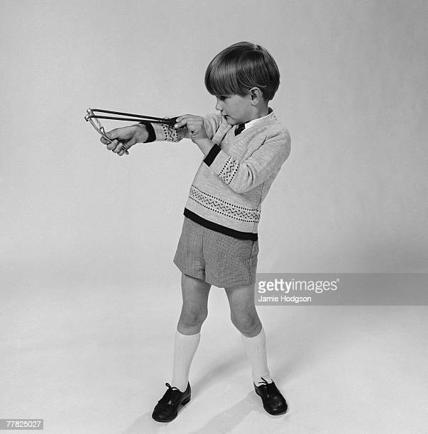A young boy in shorts playing with a catapault circa 1960