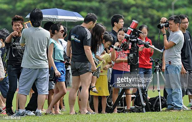 A young boy in Singapore looks through the telescope to watch the transit of Venus across the surface of the Sun on June 6 2012 Skygazers around the...