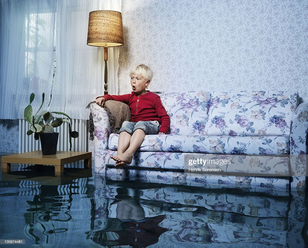 young boy in sofa in flooded room : Stock Photo