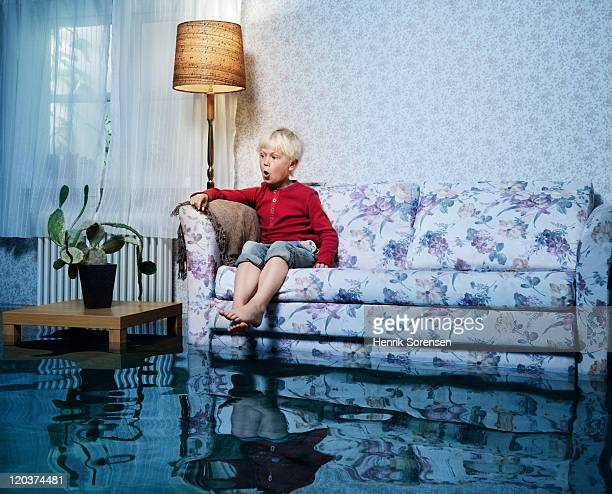 young boy in sofa in flooded room