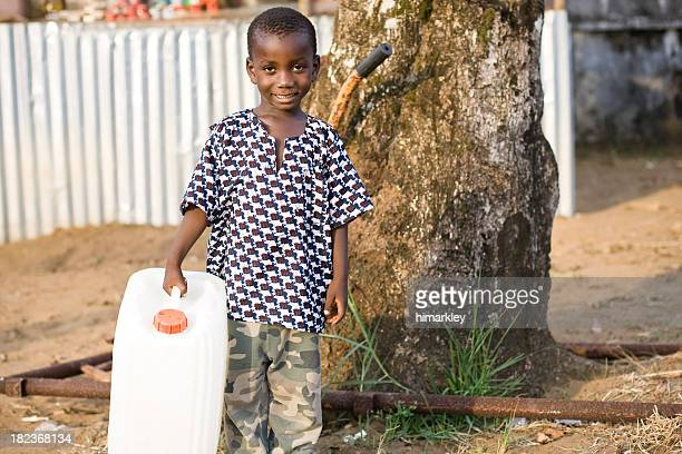 Young boy in third world country holding water jug