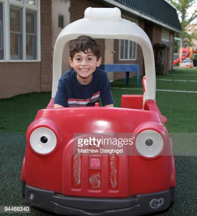 young boy in toy car on playground