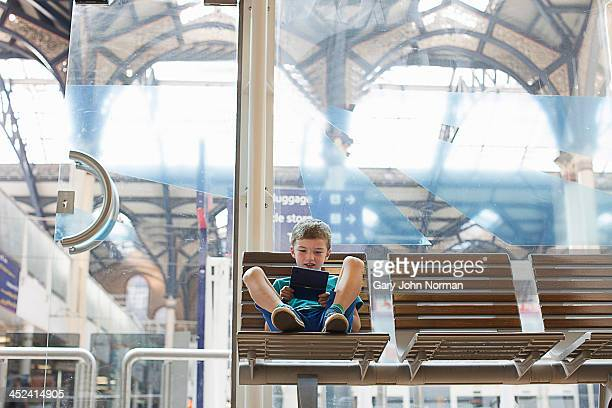 Young boy in train station waiting room playing handheld game
