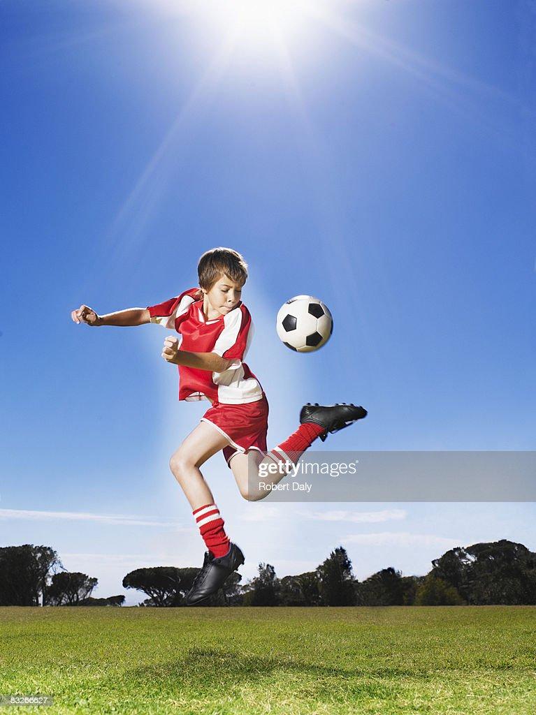 Young boy in uniform kicking soccer ball