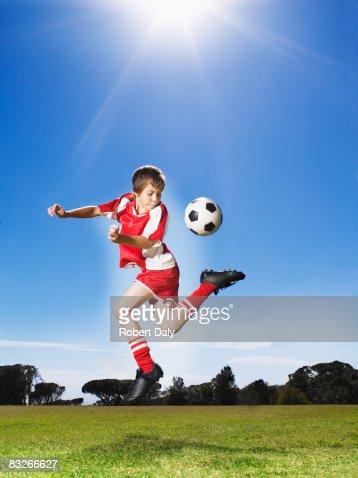 Jungen in uniform treten Fußball-Spielball