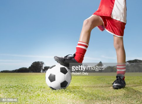 Young boy in uniform stopping soccer ball
