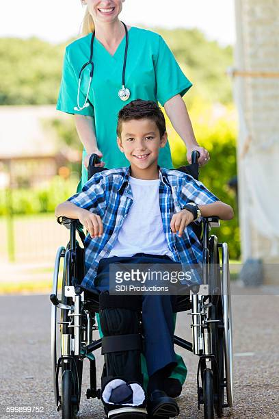 Young boy in wheelchair being pushed by a nurse