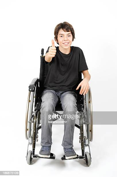 Young Boy in wheelchair giving thumb's up