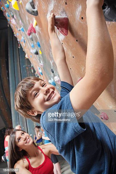 Young boy indoor rock climbing with his instructor
