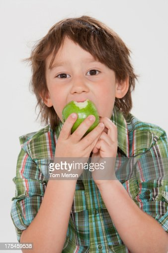 Young boy indoors eating an green apple : Stock Photo
