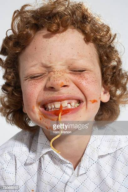 Young boy indoors eating spaghetti