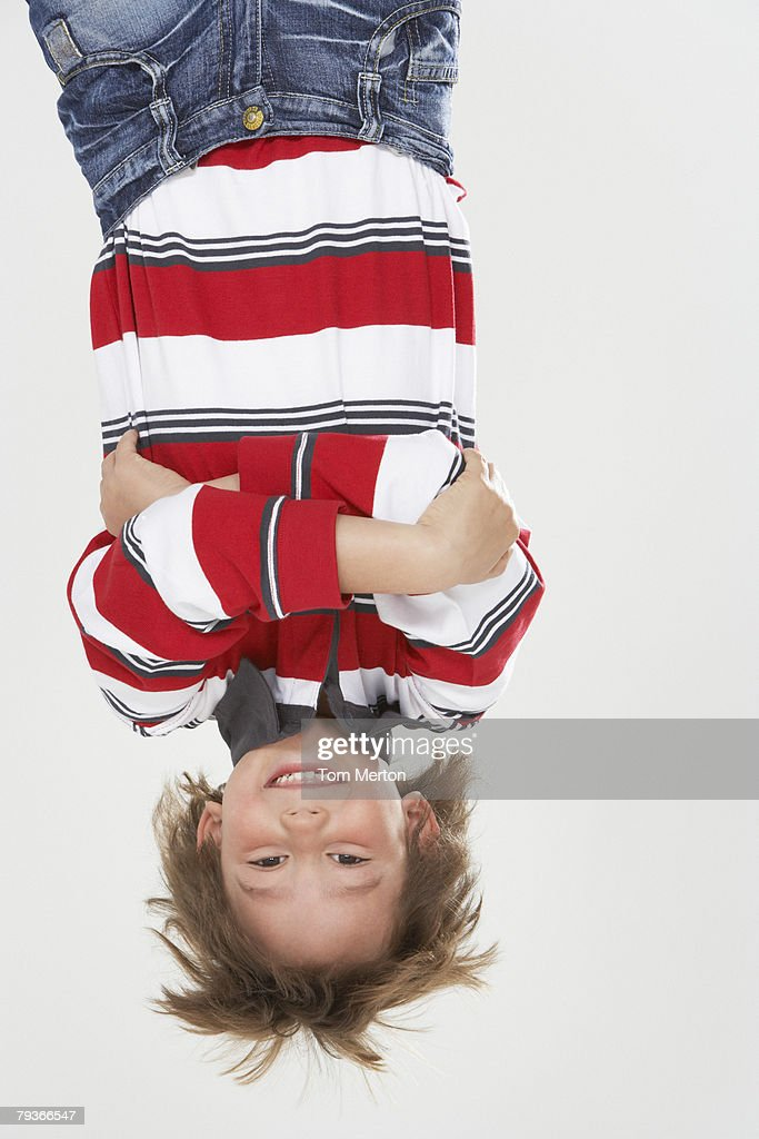 Young boy indoors hanging upside down : Stock Photo
