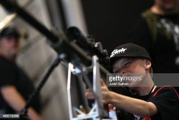 A young boy inspects a rifle during the 2015 NRA Annual Meeting Exhibits on April 10 2015 in Nashville Tennessee The annual NRA meeting and exhibit...