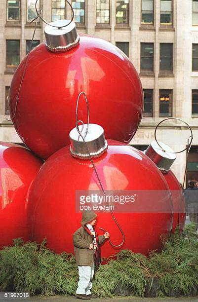 A young boy inspects a sculpture in the form of huge Christmas Tree balls 21 December 1994 in New York City's Rockefeller Center