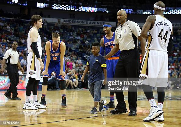 A young boy is escorted off the court after hugging Carmelo Anthony of the New York Knicks during a game against the New Orleans Pelicans during the...