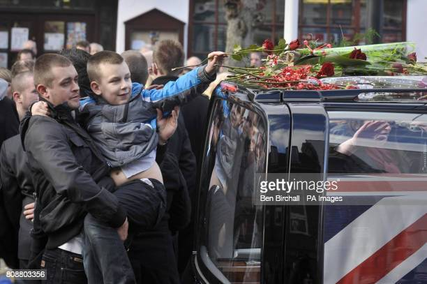 A young boy is lifted to place a single red rose on the roof of the hearse carrying the coffin of Private Martin Bell of the 2nd Battalion Parachute...