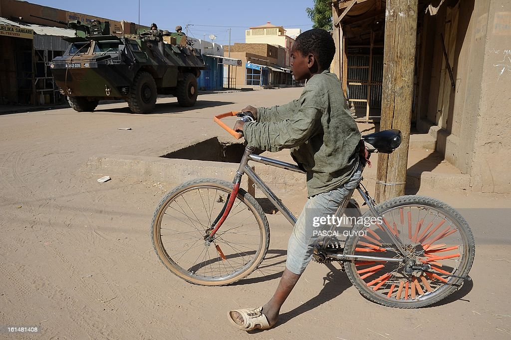 A young boy is pictured with his bicycle as French soldiers patrol aboard an armoured vehicle next to the central police station, on February 11, 2013 in Gao, one day after Islamist gunmen battled French and Malian troops. A French attack helicopter destroyed the central police station in Gao in a pre-dawn assault, after rebels from the Movement for Oneness and Jihad in West Africa (MUJAO) hiding in the building opened fire on Malian troops Sunday, sparking an hours-long street battle. AFP PHOTO / PASCAL GUYOT
