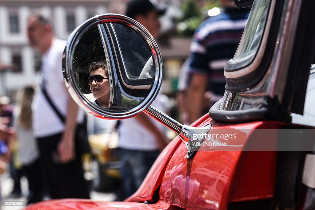 A young boy is reflected on a car mirror as he sits in a vintage car displayed during the 11th Old Timers Fest on May 29, 2016 in Prizren. / AFP / ARMEND