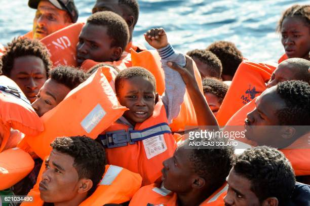 TOPSHOT A young boy is seen among the migrants and refugees seated on a rubber boat and waiting to be rescued by the Topaz Responder a rescue ship...