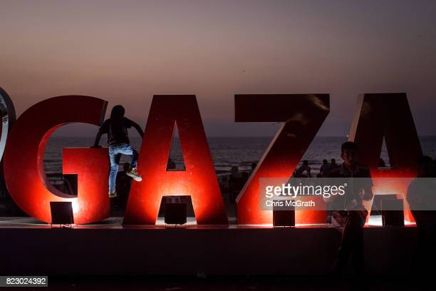 A young boy is seen climbing on a Gaza sign at the main beach on July 21 2017 in Gaza City Gaza For the past ten years Gaza residents have lived with...