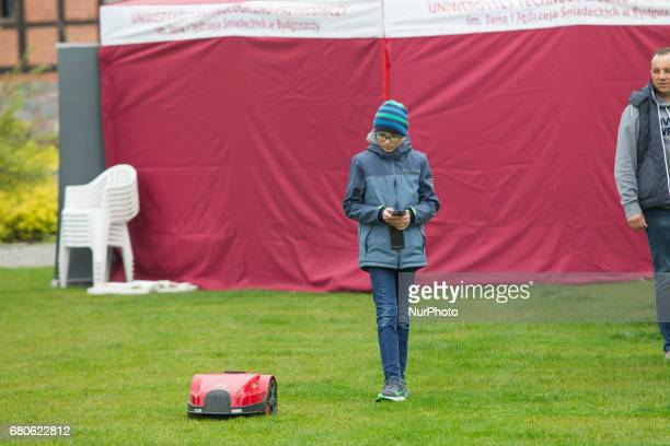 A young boy is seen remote controlling a robotic lawn mower on the Mill Island on 6 May 2017