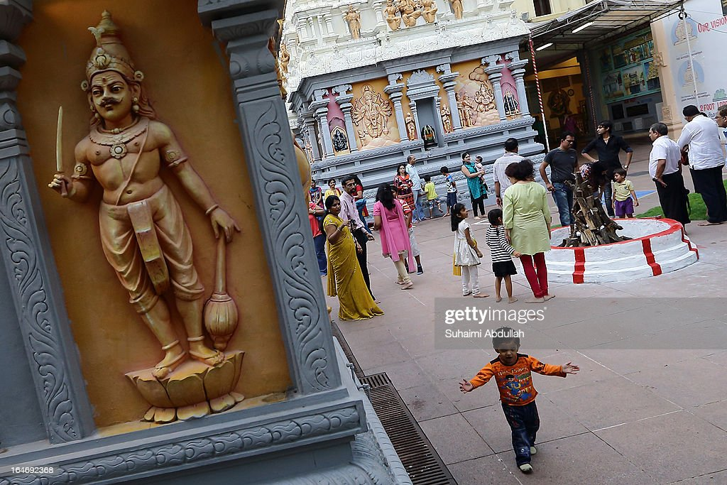 A young boy is seen running around the temple ground as people prepare to celebrate Holika Dahan on March 26, 2013 in Singapore. Holika Dahan, or burning of demon Holika, is celebrated the night before the Holi festival and is said to commemorate the escape of Prahlad (devotee of god Vishnu) from being burned when carried by Demoness Holika into fire. The bonfire epitomizes the victory of good over evil.