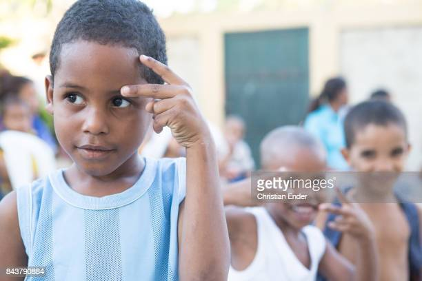 Santo Domingo Dominican Republic November 30 2012 A young boy is trying to form a sign with his fingers for the camera in the neighbourhood 'The...