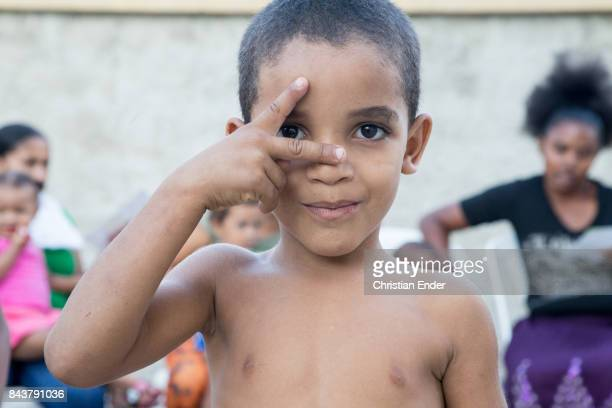 Santo Domingo Dominican Republic November 30 2012 A young boy is trying to form a sign with his fingers for the camera