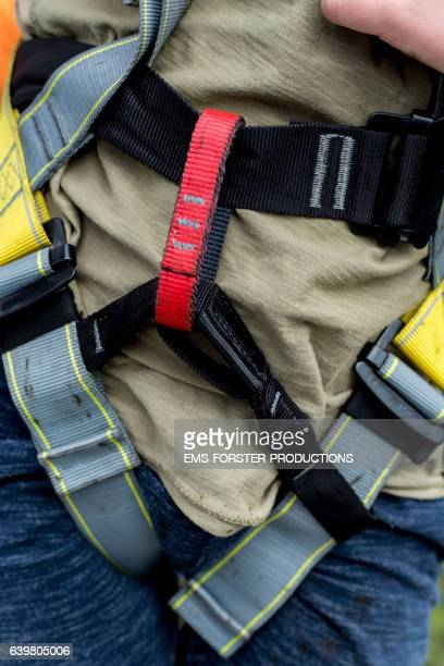 young boy is wearing safety belt for zip line activity