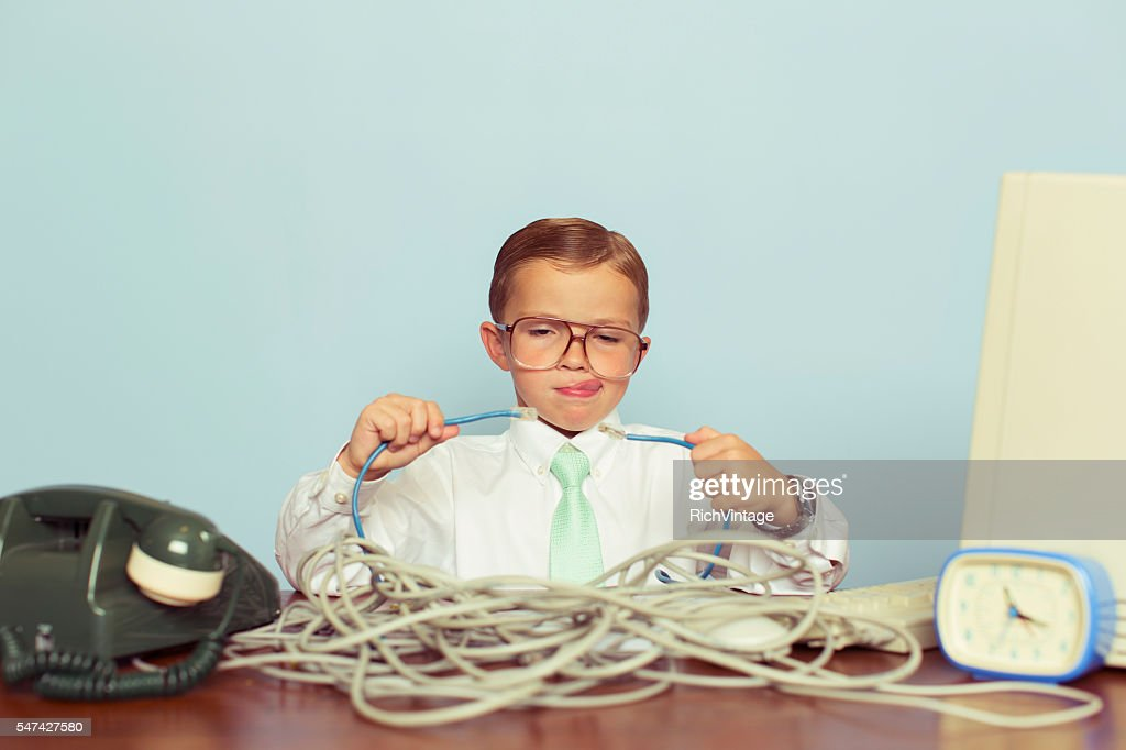 Young Boy IT Professional Smiles at Computer with Wire : Stock Photo